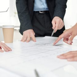 Close up of business team pointing at plans and drafts while discussing engineering project during meeting in office, copy space